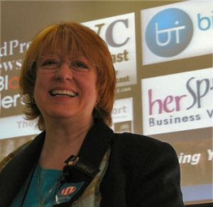 Female with red hair and wearing glasses smiling infront of a background with logo's of different companies