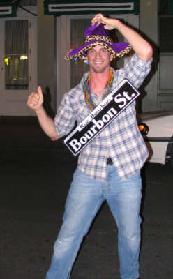 Man with stolen Bourbon Street sign on Bourbon Street, New Orleans, photograph copyright Lorelle VanFossen