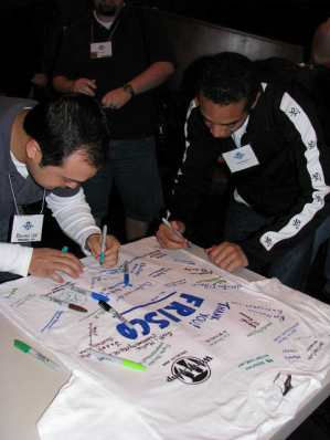 Signing a WordCamp Dallas t-shirt as a gift to the City of Frisco