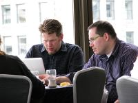 Chris Brogan and Phil Gerbyshak work on mastermind problems at their table, SOBCon 2010