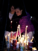 Clackamas Mall Vigil, candles set on memorial stage by two young women. Photo by Lorelle VanFossen.