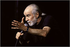 George Carlin on stage, source Wikipedia.