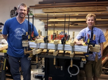 Husband and teenage nephew build a longboard skateboard in the woodshop with too many clamps, photograph by Lorelle VanFossen.